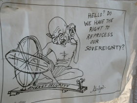 Gandhi with spinning wheel on telephone asking about sovereignty with regards to energy security.  The wheel, a symbol of India's independence itself is modified to look like the atomic symbol.